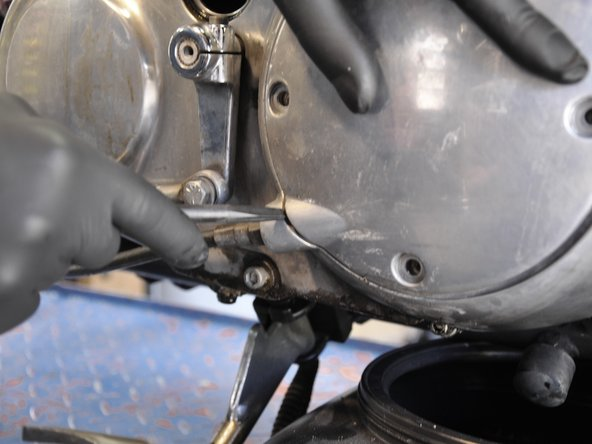 Insert a heavy duty spudger or similar prying tool into the gap between the clutch inspection cover and the transmission housing  near where clutch cable enters the housing.