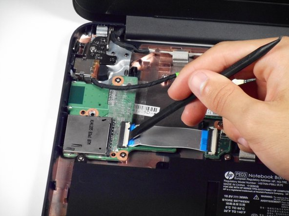 On the module, use a spudger to lift the small ZIF retaining flap for the ribbon cable connecting the SD card reader to the motherboard.
