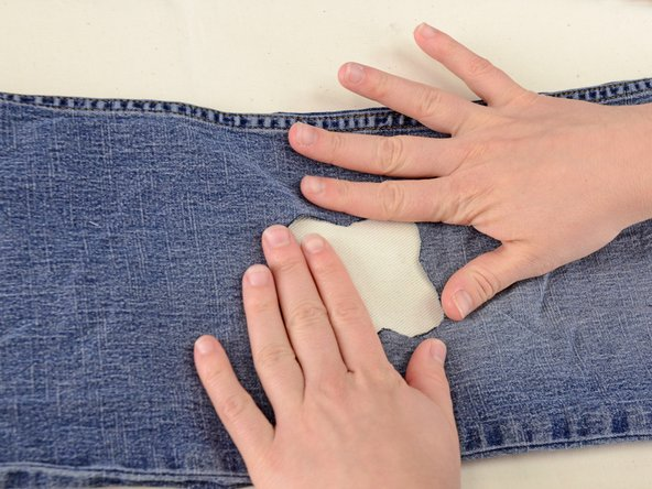 Take the scrap of fabric you will use for a patch and insert it into the hole.