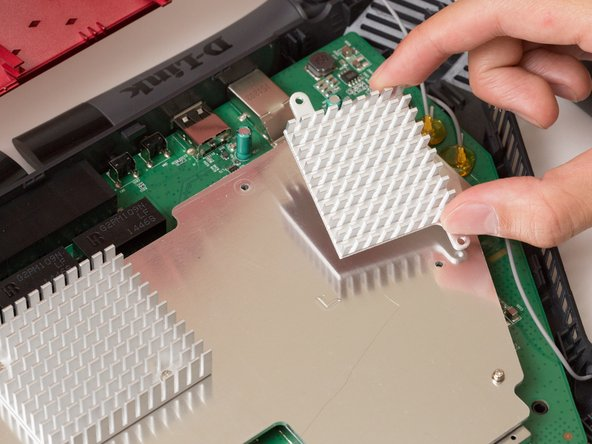 Image 3/3: Lift the heat sink off the metal plate with your fingers.