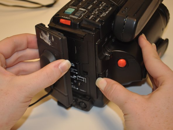 Image 1/1: Lift up to remove the battery component from the device, separating it from the camera device completely.