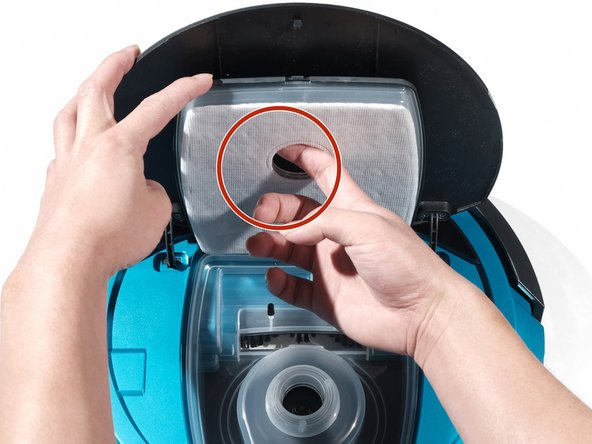 Use your finger to hook the filter through the opening near the center of the filter.