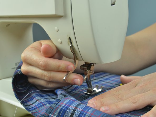 Image 3/3: Drop the presser foot. Align the first line of stitches with the needle.