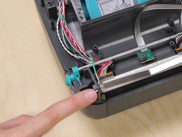 Slide the grounding cable hook toward the front of the printer to release it from the retaining spring.