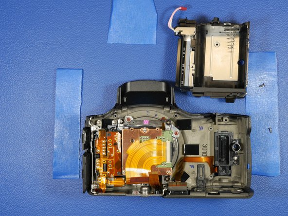 The battery compartment should just slide up and out of the camera shell.