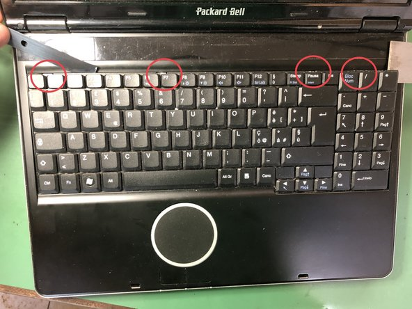 Pry in the red marked spots to release the keyboard