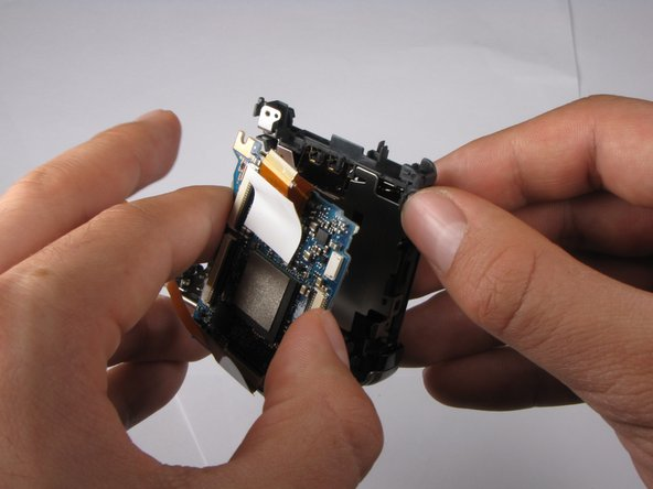 Pull back the small gray clip located on the right side of the camera to release the motherboard from its casing.