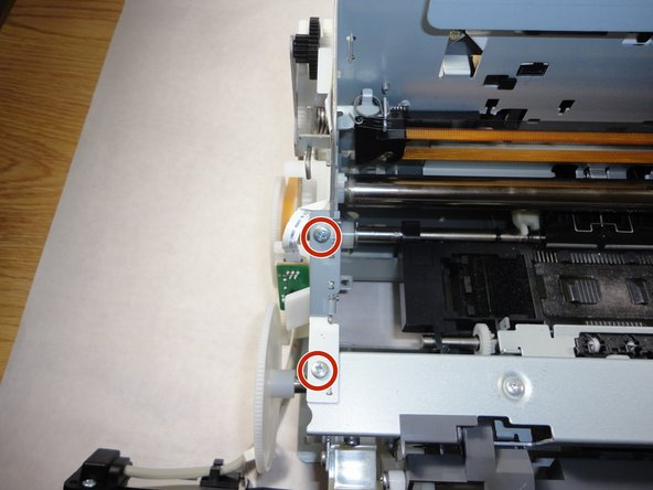 Detach the left frame support plate.  Start by removing the two 6 mm screws that secure it and then pull it out by hand.