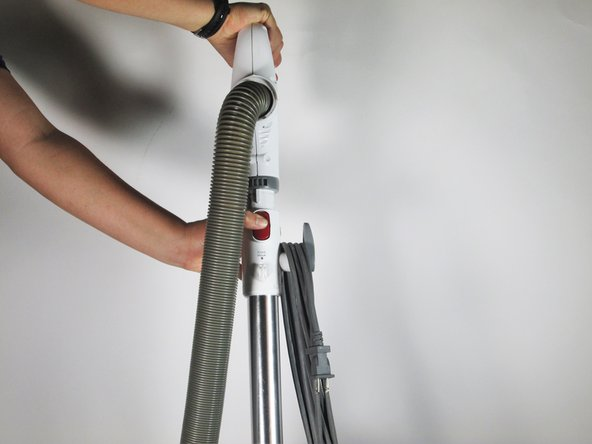 Remove the handle from the top of the vacuum with the suction hose attached.