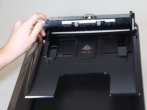 Lift the green tab to remove the fax feeder from the printer.