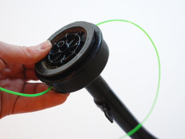 Replace the plastic piece with the cutting lines back onto the rotor, being sure that the coils remain in place, and the lines remain in place through the eyelets.