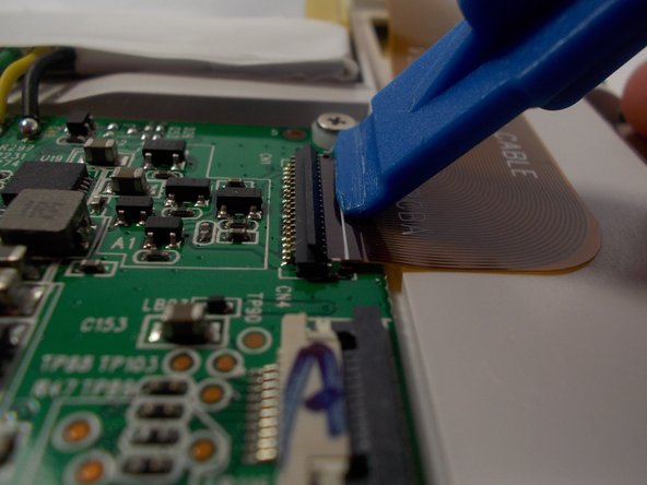 Remove the ribbon cable by lifting up on the connection with a plastic opening tool and pulling out the ribbon cable.