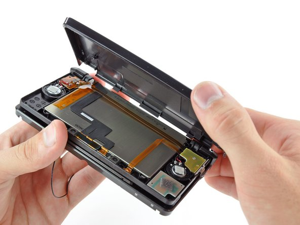 Lift the edge of the rear display bezel closest to you and rotate it towards the hinge.