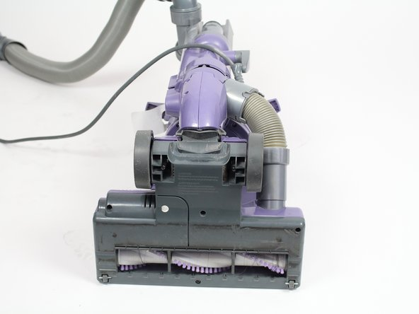 Lay down the vacuum to access the bottom panel of the roller brush compartment.