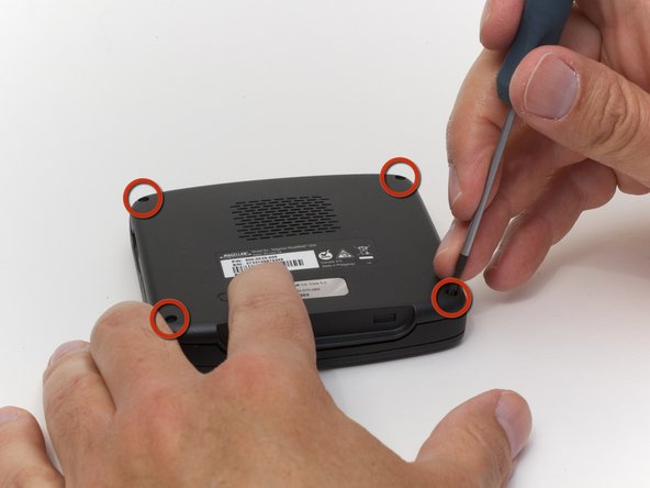 Remove the four rubber caps from the back by using the Phillips #00 screwdriver.
