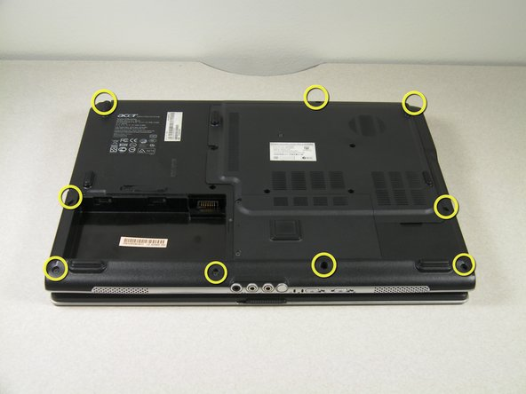On the back of the laptop, locate and unscrew all nine of the screws located at the edges.