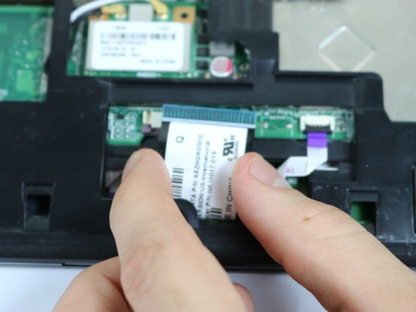 Image 2/3: Lift the black locks for the touchpad connections into the upward position.