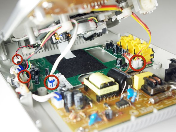 Image 1/3: Pinch the plastic adapter with two fingers to remove the wires circled in red from the circuit board.