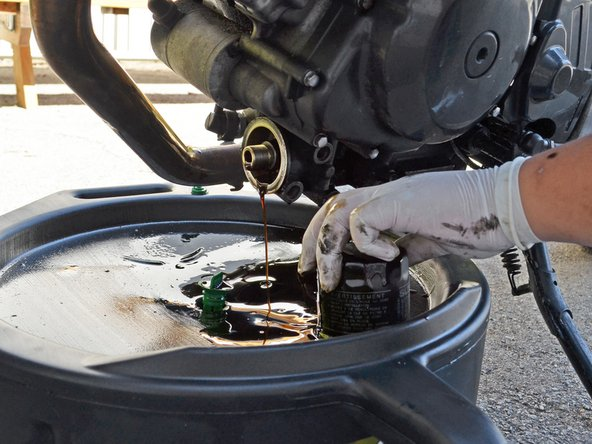 If the old oil filter is on too tightly, grasp the oil filter with an oil filter wrench and loosen it by twisting it about a half turn counter-clockwise.