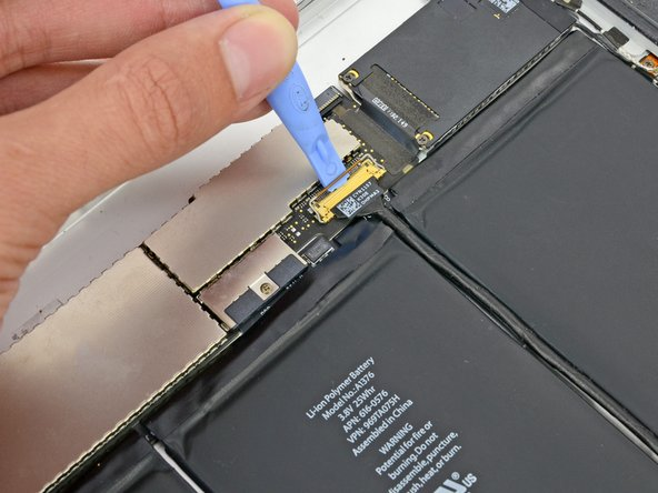 Use a plastic opening tool to flip up the retainer securing the upper component board cable connector to its socket on the logic board.