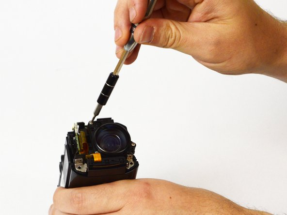 With the front of the camera facing you, locate and remove the three 5mm Phillips #00 screws that hold the lens in place.