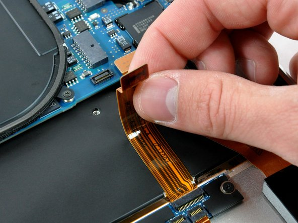 Peel the trackpad control cable off the adhesive securing it to the upper case.