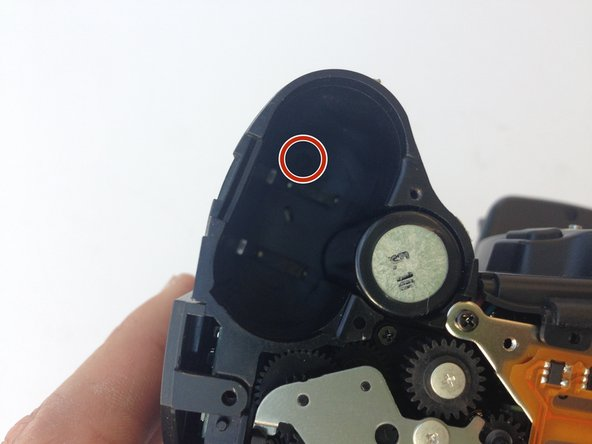 Locate the next screw by holding the camera upside down with the battery compartment empty and face up.