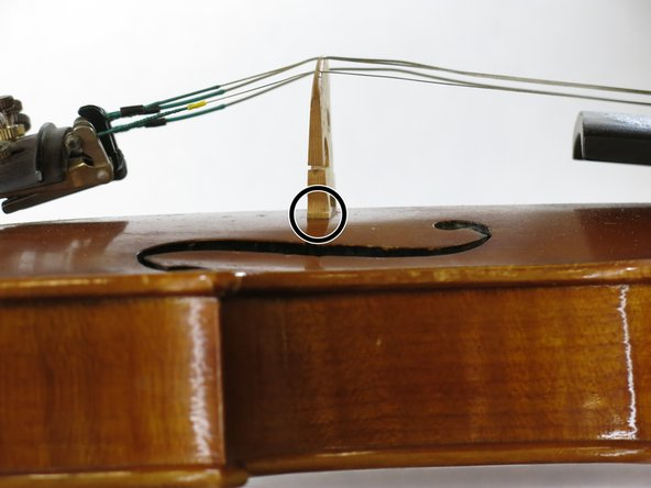 Continue to adjust the bridge to keep it perpendicular to the violin body every time you tighten the string so it is not leaning too far away from the f-holes.