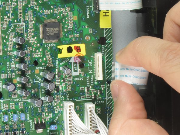 Remove the first of three ribbon cables on the left hand side of the disc drive by pulling vertically.