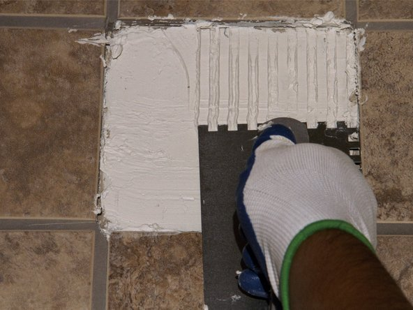 Drag the toothed end of the trowel across the adhesive to create even rows.