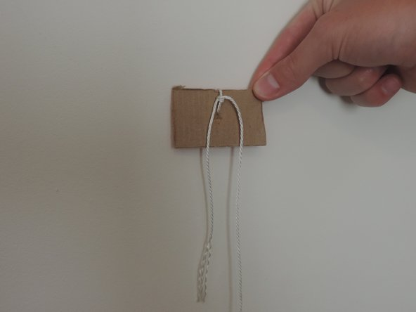 Use a scrap piece of cardboard and tie about 9 inches of string around it.