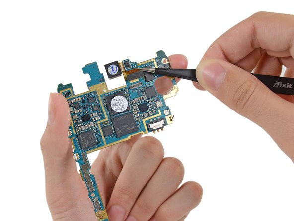 Use tweezers, or your fingers, to remove the rear-facing camera assembly.