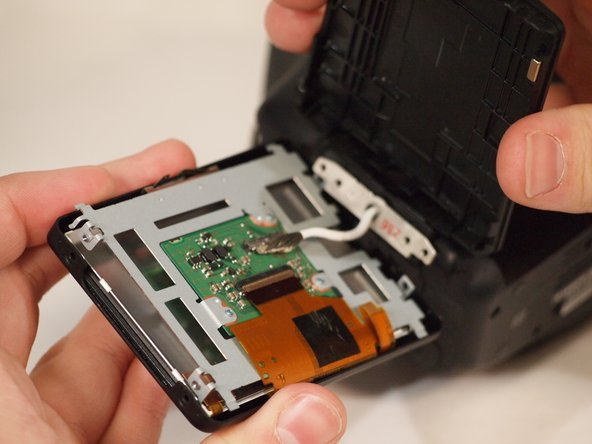 There are several components inside the casing. A board, a power cable, the screen and a ribbon cable. First, using tweezers lift the metallic clamp  connecting the ribbon to the board. WARNING. If the lever doesn't lift immediately, do not forcefully lift it. This could damage the  ribbon and board. When reapplying the ribbon, secure connection.