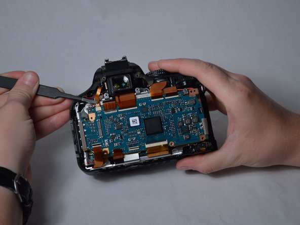 Use tweezers to remove the small cable in the top-left corner of the motherboard from its socket.