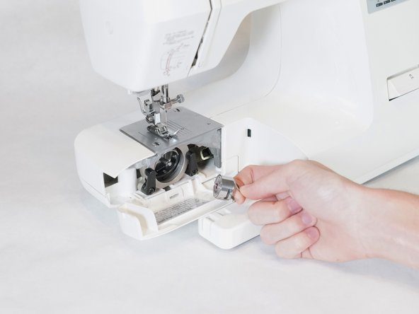 Pull on the end of the rectangular tab on the bobbin case. This will pop off the bobbin and bobbin case.