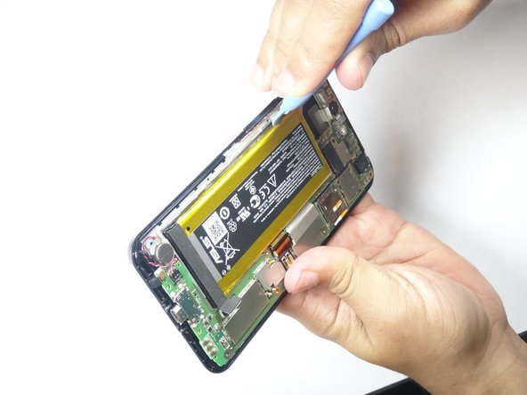 The battery pack is held on by double sided tape, you will have to apply some force when prying out the battery.