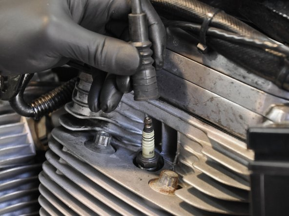 Carefully remove the spark plug wire. Do not pull on just the wire, squeeze the spark plug boot, and pull it together with the wire.