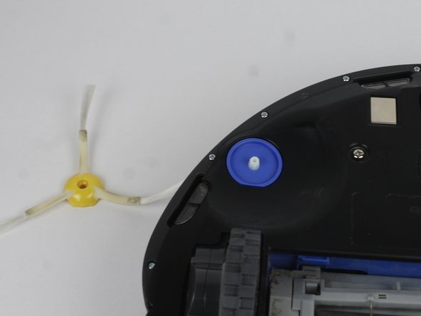 Flip over the Roomba and remove the side brush using a PH2 screwdriver.