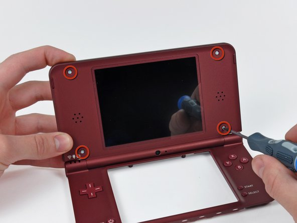 Image 2/2: Push the top outer case toward the top edge of the DSi XL, then use a spudger to pry it off the clips holding it to the inner case.