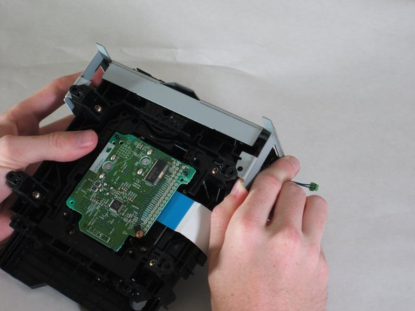 With the drive assembly separate from the player, hold as shown and pull the bracket edges away from the disk drive.