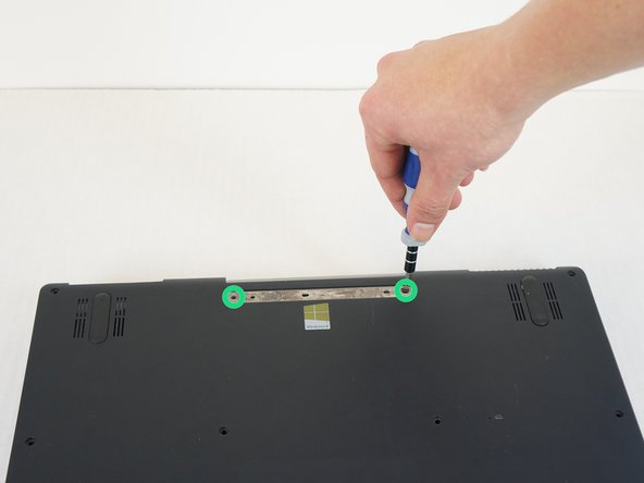 Use the blue plastic opening tool to carefully remove the rubber pad which covers the two remaining screws