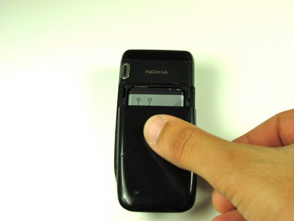 Flip over the Nokia and locate the back cover. Press your thumb on the back cover and slide it off the phone.