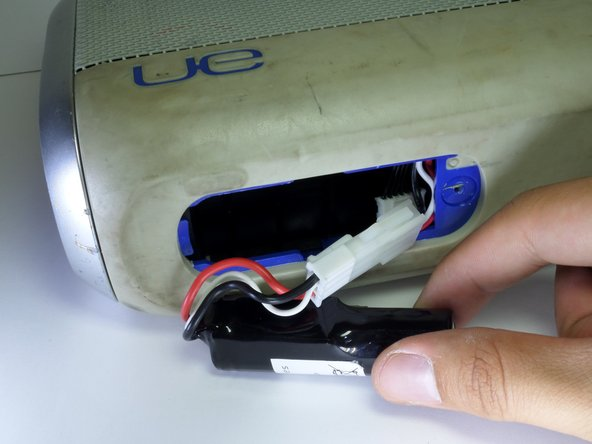 Expose the battery by gently  pulling it away from the battery cavity.