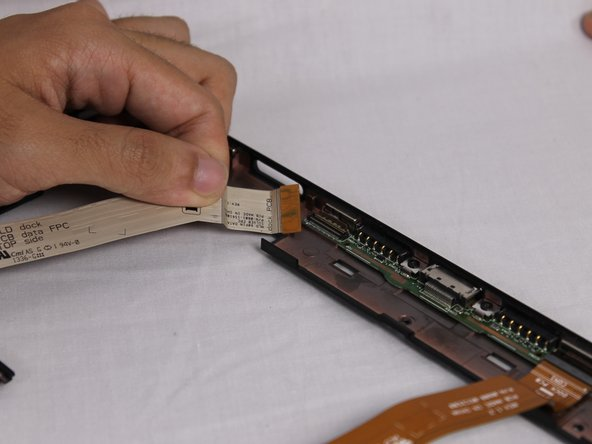 Next, you need to remove the two ribbon cables located at the bottom of the frame. To detach the first ribbon cable you need to pull straight up on the orange connecter.