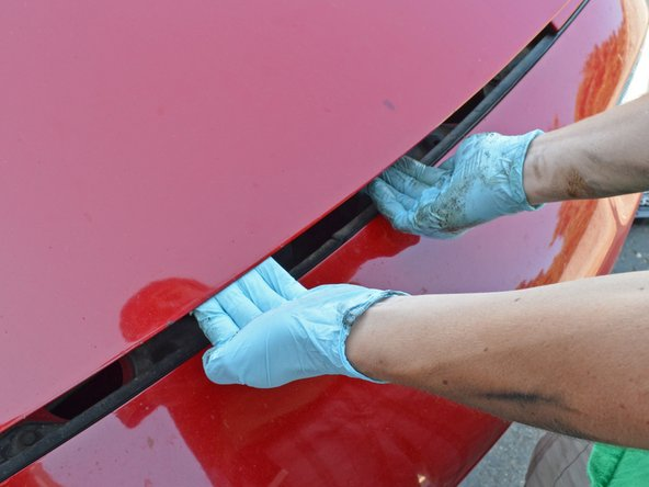 Locate the black hood catch lever just to the driver's side of the center of the hood at the front of the car.