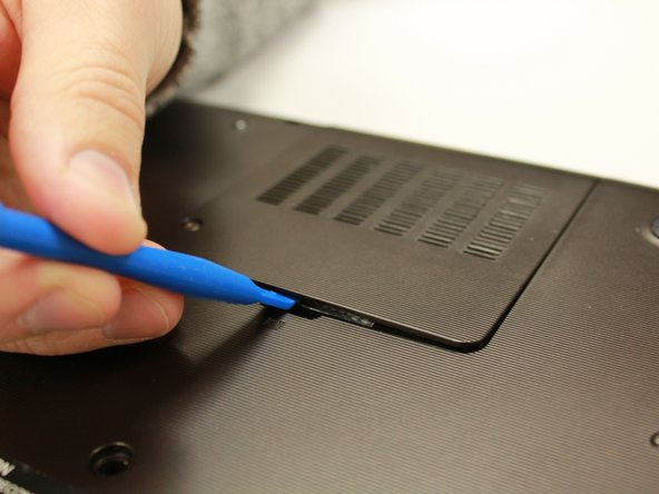 Image 3/3: Use the plastic opening tool to remove the RAM cover.