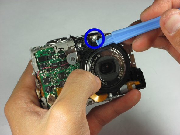 Use a spudger or a flathead screwdriver and carefully pry out the bulb located in the front of the camera on top of the camera lens.