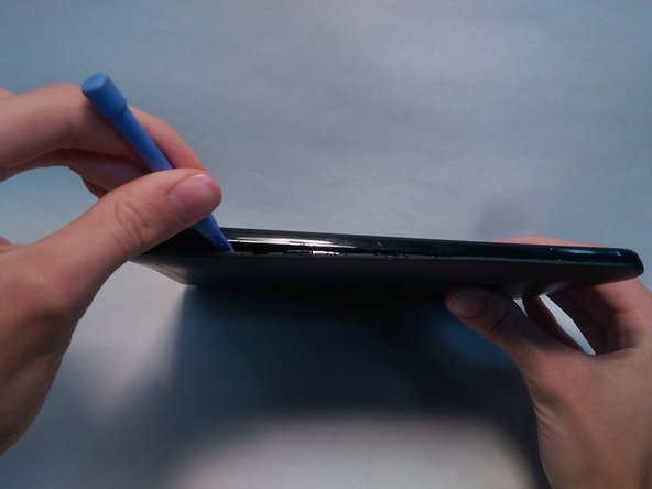 Begin by using the plastic opening tool to take off the back of the tablet.