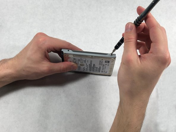 Using a Phillips #0 screwdriver, remove the four Phillips M3.0×3.5 screws (two on either side of the hard drive).