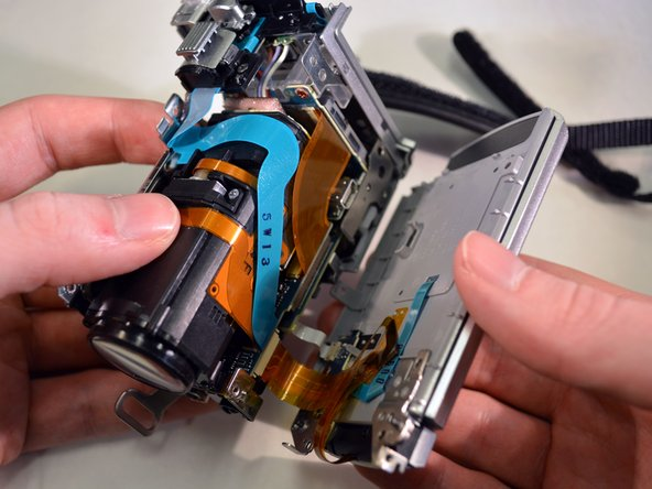 Image 3/3: Carefully pivot the unfastened left case panel (closed LCD screen) of the device until the ribbon wires are fully exposed./'''Carefully pivot the dismantled piece of the device until the ribbon wires are fully exposed'''.